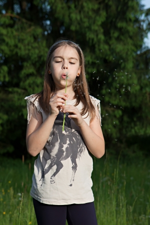 Teens girl blowing dandelion in the meadow photo