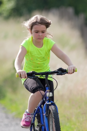 Portrait of teen girl in neon yellow shirt on a bike Stock Photo