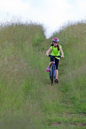 Girl teens in neon yellow shirt and a red helmet riding a bike down the meadow path