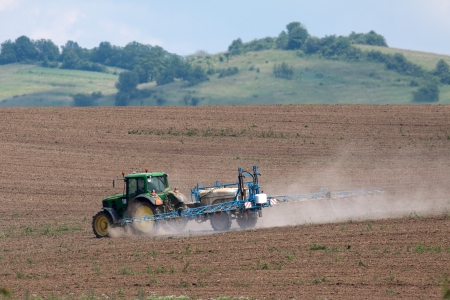 fertilisation: Tractor fertilizes the fields, in the background are hills, trees and sky Editorial