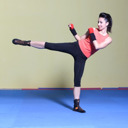 Woman practicing taebo exercises, kicking forward with legs in the gym Stock Photo - 20285338