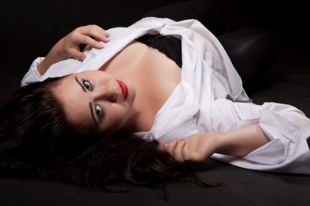 Young woman with long dark hair and red lips, in the white mens shirt with a sensual look lies on his back on the ground, on a black background Stock Photo