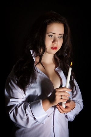 Dramatic portrait of a woman with long black hair in a white mens shirt with a burning candle on a black background photo