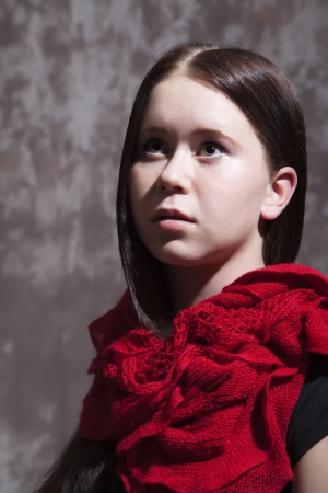 Portrait of a girl with a red scarf around his neck to look innocent