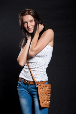 Woman with long hair in a white blouse and jeans with leather handbag holds hair on a black background