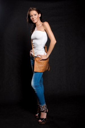 Woman with long hair in a white blouse and jeans with leather handbag posing on a black background Stock Photo