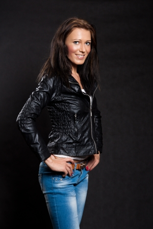 Woman with long hair in black leather jacket and jeans is smiling on black background photo