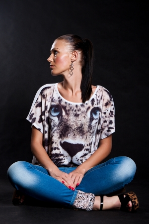 Woman with long hair in a shirt with a tiger and jeans sitting on the floor and looking sideways on a black background