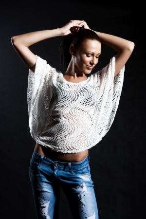 Woman with long hair in a netted shirt and jeans has closed eyes on a black background