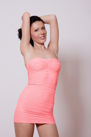 Woman in pink mini dress with long black hair posing photo