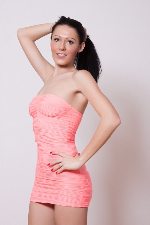 Woman in pink mini dress with long black hair posing Stock Photo