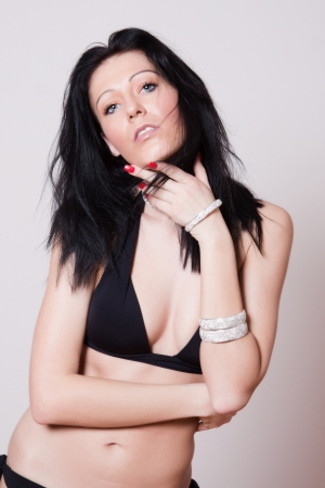 A woman in a black bikini with long black hair in a pose