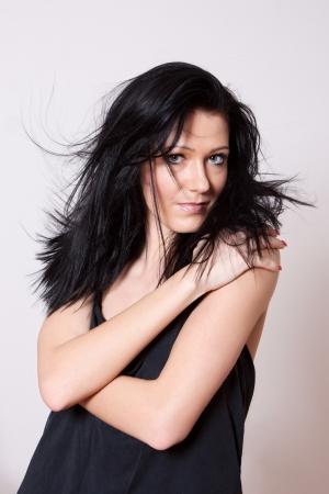 zerzaust: Frau im schwarzen Unterhemd mit langen zerzausten schwarzen Haar sieht