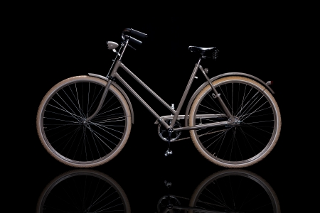 Old refurbished retro bike isolated on black background with reflection side view
