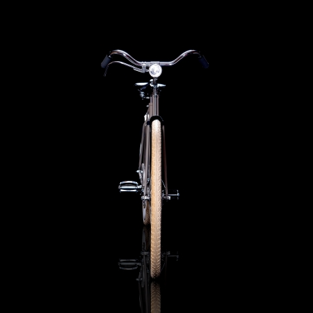 Old refurbished retro bike isolated on black background with reflection view from the front Stock Photo