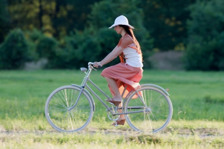 Woman in orange skirt and white hat riding on a retro bike on the meadow side view