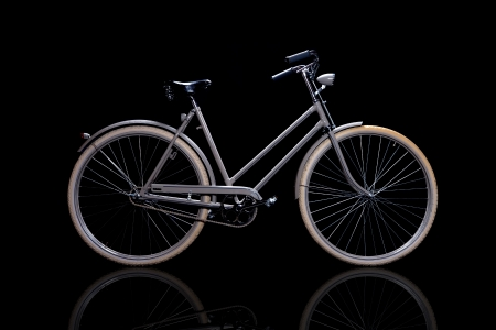 Old refurbished retro bike isolated on black background with reflection side view photo