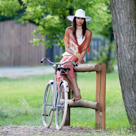 Woman in orange skirt and white hat sits on a wooden railing next to retro bicycle in meadow view from the front photo