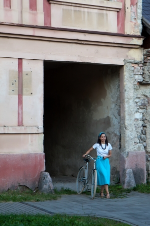 A woman in a turquoise skirt with a scarf on her head comes next to retro bicycle from old building photo