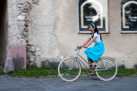 A woman in a turquoise skirt with a scarf on her head rides a retro bike next to old building