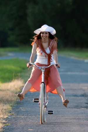 grass skirt: Woman in orange skirt and white hat riding on a retro bike in meadow view from the front