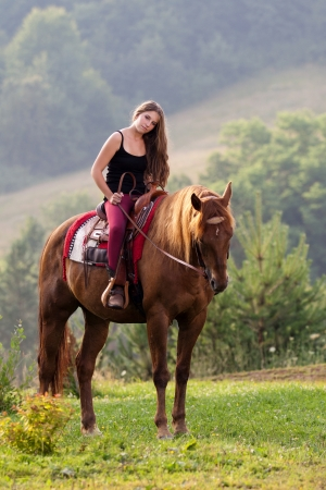 Young girl with long hair sitting on a horse breed Quarter Horse Stock Photo - 21031996