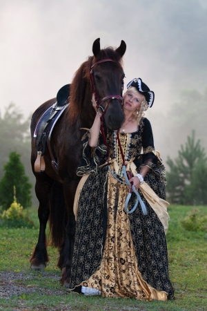 Woman in royal baroque dress, standing next to a horse in the fog