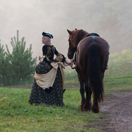Woman in royal baroque dress, walking beside a horse in the fog photo