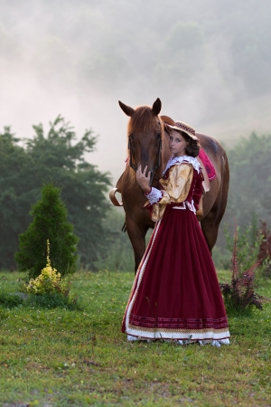 Girl in baroque dress royal, next to a horse in the fog Stock Photo