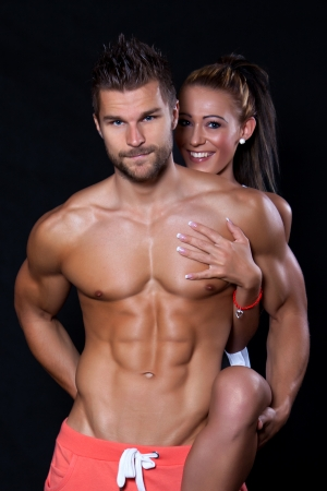 Young muscular man behind him a young woman who keeps him and her leg is through him