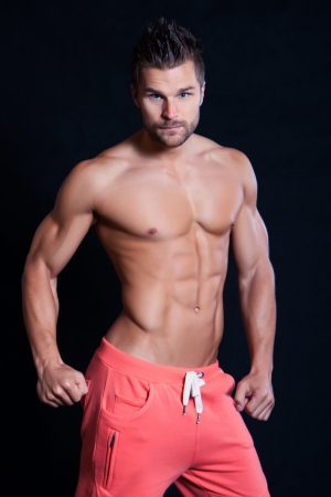 Young muscular man undressed to the waist showing his muscles on black background photo