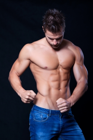 Young muscular man undressed to the waist showing his muscles on black background Stock Photo