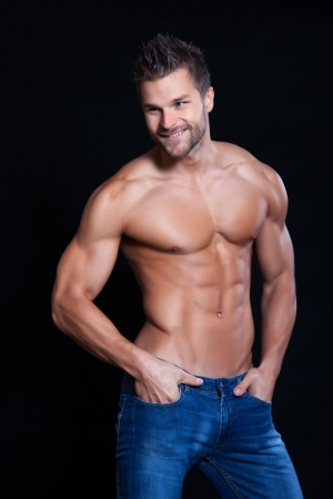 Young muscular man undressed to the waist has his hands in his pockets and smiling, on black background Stock Photo