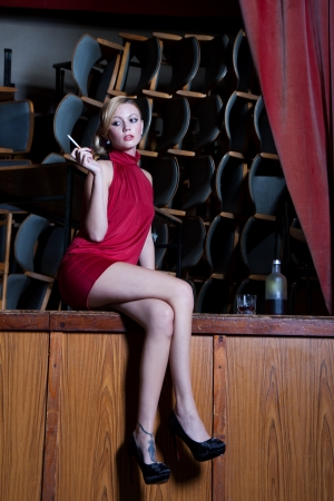 Actress young lady in red dress sits sad with a cigarette and a glass of alcohol on a dusty old stage photo