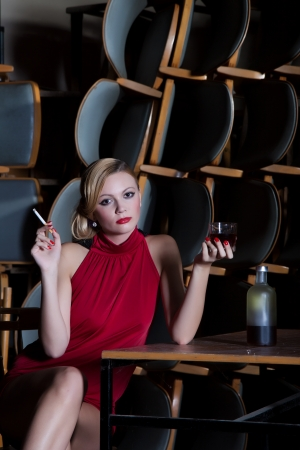 Actress in red dress sitting sad at the table with a cigarette and a glass of alcohol on a dusty old stage photo