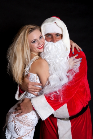 Man Santa Claus hugging a woman angel on a black background photo