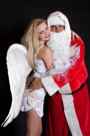 Man Santa Claus hugging a woman angel with big wings photo