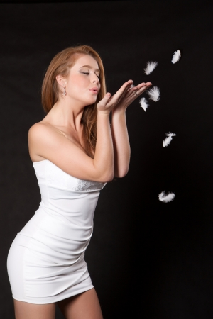 Young woman in a white mini dress blowing feather of his hands, on black background Stock Photo - 22565794