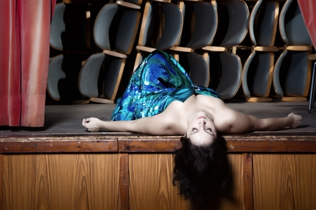 Young actress on stage in a blue dress lying on the ground and plays dead photo