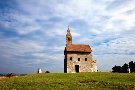 Old Church on a grassy hill with cloudy skies