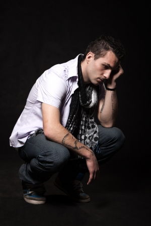 Young man in shirt is sad squatting on a black background