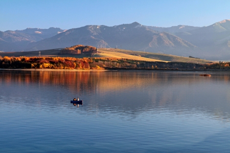 Fishers on a boat on the dam, mountains in the background, with reflection of autumn trees