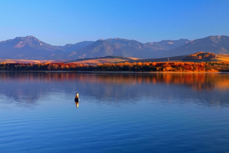 Fishers on a boat on the dam, mountains in the background, with reflection of autumn trees photo