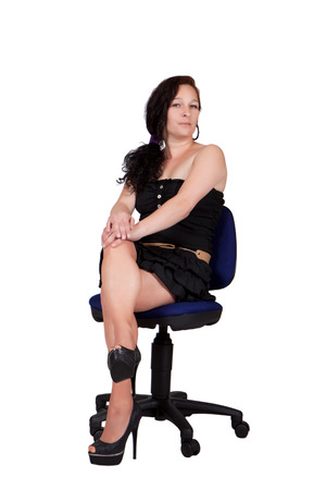 swivel: Long-haired woman in black dress sitting on an office chair rotatable Stock Photo