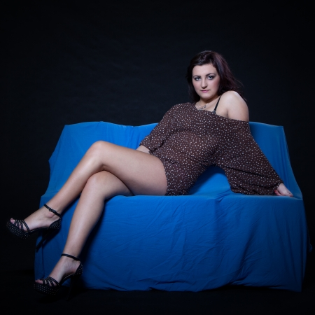 Young woman in sexy dotted mini dress lying on blue sofa