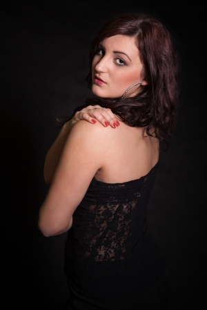 Portrait of long-haired brunette in a black dress photo