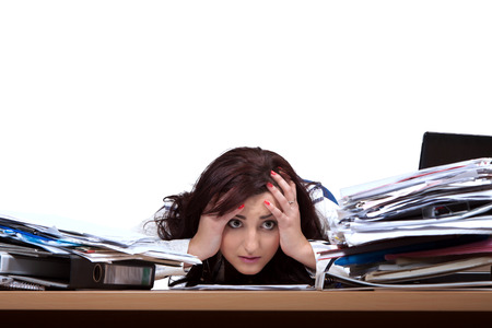 Young female office worker helplessly looking at the pile of papers with place for text photo