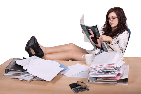 front desk: Young female office worker sitting with feet on desk with pile of paper and reads magazine, where she is on the front page