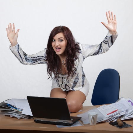 Young female office worker sitting on desk at laptop with hands up photo