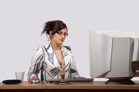 Young female office worker is concerned to work on computer